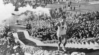 Atleta carrega tocha olímpica na abertura das Olimpíadas de Tóquio de 1964