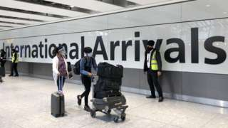 Passengers are escorted through the arrivals area of terminal 5 towards coaches destined for quarantine hotels