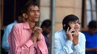 2020 మార్చి 9వ తేదీన బాంబే స్టాక్ ఎక్స్చేంజ్ భవనం వద్ద షేర్లను చూస్తున్న వ్యక్తులు