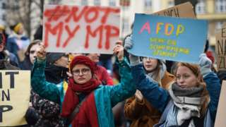 """Young people in Erfurt hold placards reading """"Not my MP"""" (L) and """"A FD P"""" on 6 Feb 2019"""