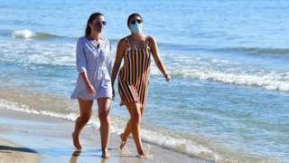 Women in masks walking along the beach
