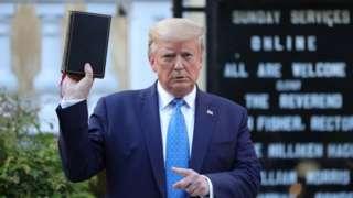 Donald Trump com Bíblia em frente a igreja