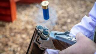 A blue shotgun cartridge jumps into the air, ejected from the smoking barrel of a shotgun broken open on its hinge to reload