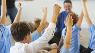 Children with raised hands in a clasroom
