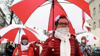 Женщины с бело-красными зонтиками