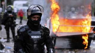 A police officer in riot gear looks on during clashed with demonstrators during a protest organized in reaction to the killing of lawyer Javier Ordonez, in Bogota, Colombia, 09 September 2020.