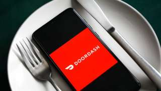 A mobile phone showing the DoorDash logo sits between a fork and a knife on top of a dinner plate