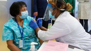 A health-care worker administers the second dose of the Pfizer-BioNTech vaccine in Toronto, Canada