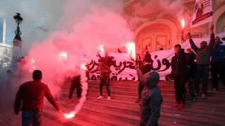 Tunisian protesters light flares and shout slogans during a celebration to mark the seventh anniversary of the uprising that ousted president Zine El Abidine Ben Ali