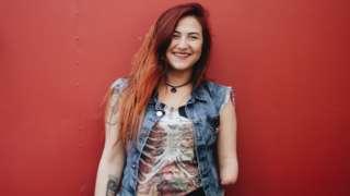 Mariana Torquato sorrindo em frente a parede vermelha