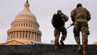 National Guard members walk at the Capitol in Washington on January 15, 2021