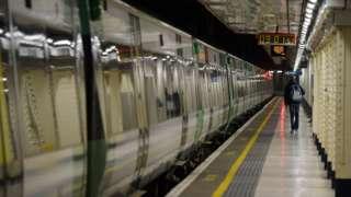A man walks alongside a stationary train on an empty platform at London Victoria