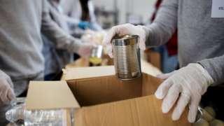 Duas pessoas em frente a caixa de papelão apoiada em mesa com comida dentro; uma das pessoas coloca uma lata na caixa