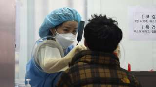 A medical professional takes samples from people at a testing centre in Seoul