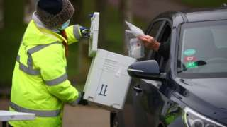 A worker collects a swab from a car window at a test centre