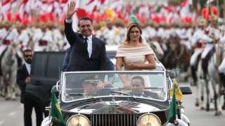 Jair Bolsonaro waves as he drives past in Brasilia, Brazil, January 1, 2019
