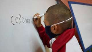 "Student Juan Camacho writes the word ""coronavirus"" on a whiteboard during a lesson at Escuela 30, a rural school that has resumed classes after a month off due to the coronavirus disease (COVID-19), in San Jose, Uruguay April 22, 2020"