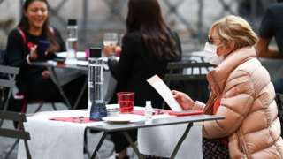 A woman reads a menu as she sits at a restaurant terrace in Rome, on October 25, 2020