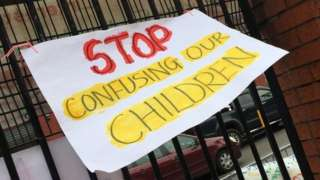 A 'Stop confusing our children' sign on the iron railings outside the school