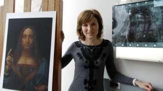 Fiona Bruce in conservation studio in New York with print of Salvator Mundi (newly discovered Leonardo da Vinci painting)