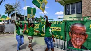 Supporters of presidential candidate David Granger, of the National Unity and Alliance for Change (ANPU-AFC) party, cheer and wave flags in front of their house in Georgetown, Guyana, on 1 March, 2020.