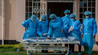 People in personal protective equipment are seen at a lodging building readying for their turn to go and work inside the main COVID-19 treatment center at Kamuzu Central Hospital in Lilongwe, Malawi, on January 18, 2021.