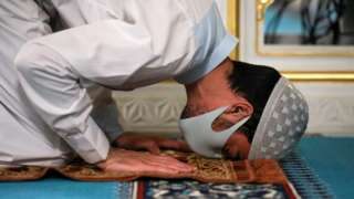 A man prays whilst wearing a face mask