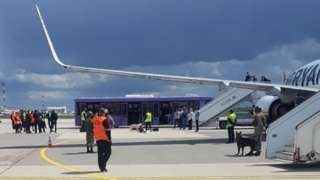 Airport personnel and security forces are seen on the tarmac in front of a Ryanair flight which was forced to land in Minsk, Belarus. Photo: 23 May 2021