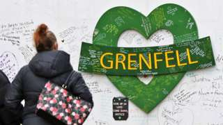 A woman walks towards the Grenfell Memorial Wall in the grounds of Kensington Aldridge Academy in February 2021