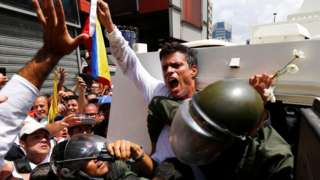 Venezuelan opposition figure Leopoldo López gets into a National Guard armoured vehicle in Caracas, 18 February 2014