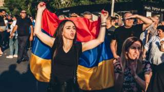 A supporter of Nikol Pashinyan main candidate of the Civil Contract party for the parliamentary elections is seen with the Armenian flag
