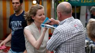 A passerby takes leaflets from the hand of Les Republicains (LR) party candidate Nathalie Kosciusko-Morizet during an altercation while campaigning in the 5th arrondissement in Paris on June 15, 2017,