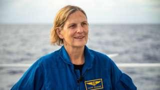 Kathy Sullivan a bordo de um barco, com mar visto ao fundo