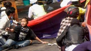 Protesters lie on the ground in Myanmar after troops opened fire