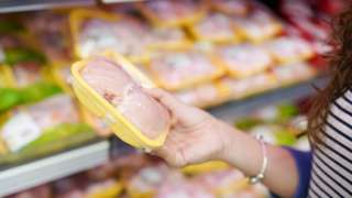 mulher segurando cartela com filés de frango