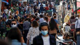 People wear masks while walking along a busy Paris street
