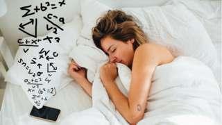 امرأة نائمة بينما يجري هاتفها عمليات حسابية