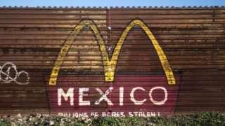 """Un pedazo del muro que separa a México del suroeste de EE.UU. con un grafiti del logo de McDonald's y la palabra """"México""""."""