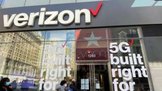 People wait in line at a Verizon store during the coronavirus pandemic.