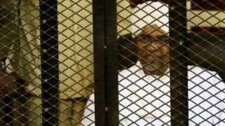 عمر البشیر د محاکمې پر مهال په یوه پنجره کې ناست و