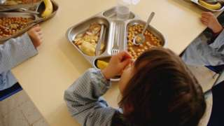 Children eating canteen food in a school hall