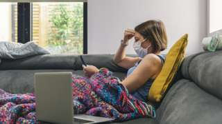 Woman wearing mask on sofa