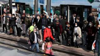 People wait in a queue at Cevizlibag district to get on metrobuses and trams to return their homes on 29 April