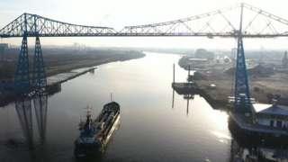 Dredger sails beneath bridge