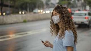 Mulher usando máscara em rua de São Paulo