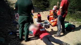 Rescuers attend to the injured cyclist