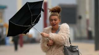 A woman's umbrella turns inside-out in strong winds