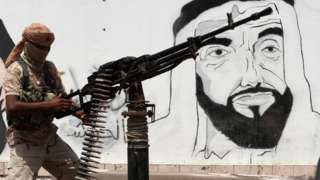 UAE-backed Yemeni pro-government fighter mans a machine-gun next to a mural in Mukalla showing the UAE's late founder and president, Sheikh Zayed bin Sultan Al Nahyan (8 August 2018)