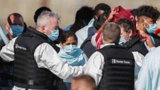 UK Border Force officials working with migrants brought into Dover harbour on Thursday