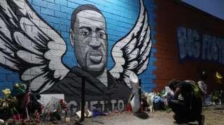 Un homme à genoux devant un mémorial et une peinture murale pour George Floyd